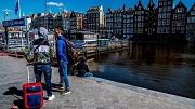 2018-05-02 00:00:00 AMSTERDAM - Toeristen met rolkoffers bij de opstapplek voor rondvaartboten bij Amsterdam Centraal. ANP ROBIN UTRECHT